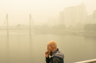 PORTLAND, OR - SEPTEMBER 12: Declan Mulvey smokes a cigarette on the Morrison Bridge despite heavy smoke on September 12, 2020 in Portland, Oregon. Multiple wildfires grew by hundreds of thousands of acres this week, covering large portions of the West coast in smoke.   Nathan Howard/Getty Images/AFP