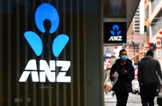 A man walks past an ANZ bank sign in Melbourne's Chinatown on April 30, 2020. - Australia's ANZ Bank announced a 50-percent dive in after-tax profits, as the lender set aside one billion Australia dollars (655 million US) to cover expected losses resulting from the coronavirus fallout. (Photo by William WEST / AFP)