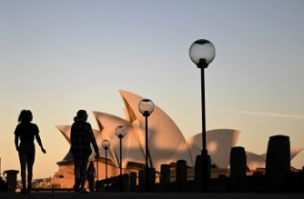 Sunset hues fall on the landmark Sydney Opera House as visitors walk past as on Circular Quay, usually packed with tourists, in Sydney on June 16, 2020. (Photo by Saeed KHAN / AFP)