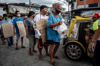 (File photo) Jeepney drivers wearing face masks queue up to receive food aid from a concerned resident on a road a in Manila on August 6, 2020. - The Philippines plunged into recession after its biggest quarterly contraction on record, data showed on August 6, as the economy reels from coronavirus lockdowns that have wrecked businesses and thrown millions out of work. (Photo by Lisa Marie David / AFP)