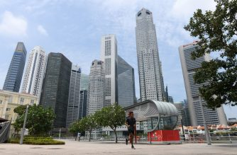 A man jogs along the Singapore River, as the financial business district is seen in the background, in Singapore on August 11, 2020. - Singapore's virus-hammered economy shrank almost 43 percent in the second quarter, in a sign that the country's first recession in more than a decade was deeper than initially estimated, official data showed on August 11. (Photo by Roslan RAHMAN / AFP)