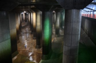 "In this photo taken on September 3, 2020, an employee walks in the water tank of the metropolitan outer underground discharge channel in Kasukabe, Saitama prefecture. - It has been called Japan's underground ""Parthenon,"" a cavernous complex charged with protecting Tokyo and surrounding areas from catastrophic flooding -- a risk experts warn is growing as climate change advances. (Photo by Charly TRIBALLEAU / AFP) / TO GO WITH JAPAN-WEATHER-FLOOD-TYPHOON,FOCUS BY SHINGO ITO"