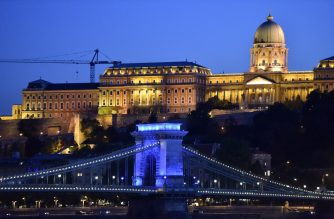 As part of a conference about the live events in the coronavirus situation, the oldest Hungarian bridge, the 'Lanchid' (Chain Bridge) is illuminated by blue light in Budapest on September 9, 2020. - The conference, the 'Power of live events' will be held in the conference hall of Puskas Arena on September 10. (Photo by ATTILA KISBENEDEK / AFP)