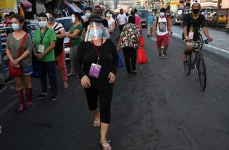 In this photo taken on September 19, 2020, people wearing face shields queue up at a public market in Manila. - Many face the new normal in the Philippines, where it is now compulsory to wear both face masks and plastic shields in indoor public spaces and on public transport to curb the spread of the COVID-19 coronavirus. (Photo by Ted ALJIBE / AFP) / TO GO WITH Health-virus-Philippines,PHOTOESSAY