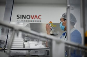 A staff member works during a media tour of a new factory built to produce a COVID-19 coronavirus vaccine at Sinovac, one of 11 Chinese companies approved to carry out clinical trials of potential coronavirus vaccines, in Beijing on September 24, 2020. (Photo by WANG ZHAO / AFP)