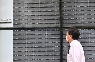 A man walks past an electronic board which normally displays stock prices at the Tokyo Stock Exchange but is empty after trading was halted due to a glitch in Tokyo on October 1, 2020. (Photo by CHARLY TRIBALLEAU / AFP)
