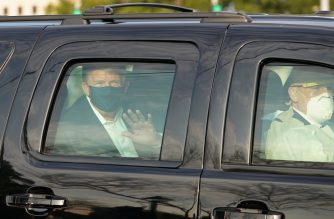 US President Trump waves from the back of a car in a motorcade outside of Walter Reed Medical Center in Bethesda, Maryland on October 4, 2020. (Photo by ALEX EDELMAN / AFP)