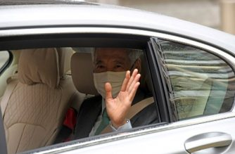 Singapore's Prime Minister Lee Hsien Loong waves as he arrives in a car at the High Court in Singapore on October 6, 2020. (Photo by ROSLAN RAHMAN / AFP)