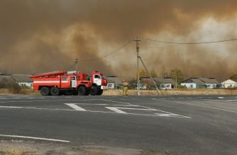 "Smoke rises from a fire at a munitions depot as fire engines are seen on a road in the Ryazan region on October 7, 2020. - Russia on October 7 evacuated more than 1,000 people from nearby villages after a wildfire set off explosions at a munitions depot in the Ryazan region southeast of Moscow, officials said. (Photo by Handout / Russian Emergencies Ministry / AFP) / RESTRICTED TO EDITORIAL USE - MANDATORY CREDIT ""AFP PHOTO / Russian Emergencies Ministry / handout "" - NO MARKETING - NO ADVERTISING CAMPAIGNS - DISTRIBUTED AS A SERVICE TO CLIENTS"