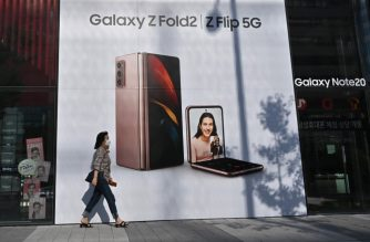 A woman walks past an advertisement for the Samsung Galaxy Z Fold2 and Z Flip smartphones at a Samsung Electronics store in Seoul on October 8, 2020 as the electronics giant flagged a leap of nearly 60 percent in third-quarter operating profits. (Photo by Jung Yeon-je / AFP)