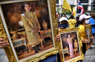 Royalist supporters from the United Group to Protect Monarchy holding images King Maha Vajiralongkorn (L) and Queen Suthida stage a rally against former opposition Future Forward Party leader Thanathorn Juangroongruangkit's who have attended anti-government protests, in Bangkok on October 12, 2020. (Photo by Lillian SUWANRUMPHA / AFP)