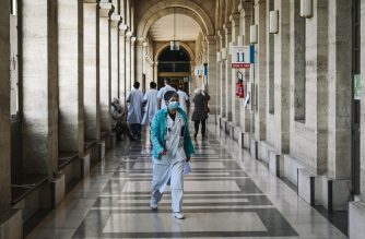 A medical staff member walks inside the main alley of the Lariboisiere Hospital of the AP-HP (Assistance Publique - Hopitaux de Paris) in Paris, on October 14, 2020. (Photo by LUCAS BARIOULET / AFP)