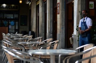 A waiter waits for customers at a restaurant in Barcelona on October 14, 2020. - Bars and restaurants are to be closed across Spain's northeastern Catalonia region for the next 15 days to slow rising coronavirus infections, the regional government said. (Photo by LLUIS GENE / AFP)
