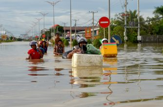 People walk through floodwaters on the outskirts of Phnom Penh on October 17, 2020. (Photo by TANG CHHIN Sothy / AFP)