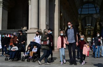 People wearing protective masks walk across the Galleria Vittorio Emanuele II in Milan on October 17, 2020, amid the Covid-19 pandemic. - Italy's government has made it mandatory to wear face protection outdoors, in an attempt to counter the spread of the coronavirus Covid-19 pandemic. (Photo by MIGUEL MEDINA / AFP)