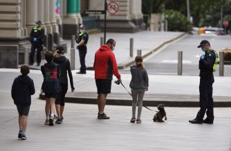 A family enjoy a walk in Melbourne on October 18, 2020, as the state government announces a lifting of some restrictions as the city battles a second wave of the Covid-19 coronavirus. (Photo by William WEST / AFP)