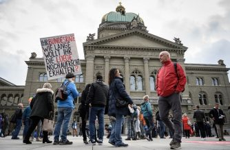 "A man holds a placard reading in German ""Your Federal Council (Swiss Government) how long do you intend to keep up the lies"" during a protest against the new measures against the Covid-19 in front of the House of Parliament on October 18, 2020 in Bern. - The Swiss government said on October 18 it was making the wearing of masks in indoor public spaces compulsory under new measures introduced after a ""worrying"" rise in coronavirus infections. It said gatherings of more than 15 people in public would also be banned under the rules to take effect on October 19, while service in restaurants and bars would be restricted to seated customers only. (Photo by Fabrice COFFRINI / AFP)"