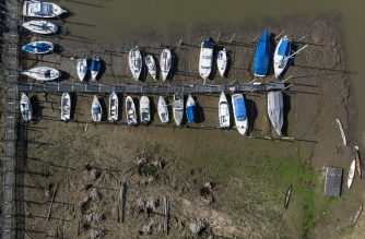 (FILES) This file picture taken on August 4, 2020 show vessels stranded on the banks of the Parana River as a consequence of a severe drought, in the Argentine city of Rosario, Santa Fe Province. - Exacerbated by a historic drought larges swathes of forest and wetlands in central South America known for their exceptional biodiversity have been ravaged by devastating fires. Experts say that the situation in this region that spans four countries -- Argentina, Brazil, Bolivia and Paraguay -- where three rivers -- Paraguay, Parana and Uruguay -- merge has become particularly critical in 2020. (Photo by Marcelo MANERA / AFP)