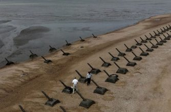 This picture taken on October 20, 2020 show tourists visiting the anti landing spikes on the coast of Kinmen, the front line islands of Taiwan. (Photo by Sam Yeh / AFP)