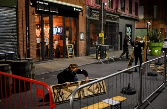 A member of staff packs up equipment outside a bar at closing time in Manchester city centre, northwest England on October 22, 2020 ahead of new coronavirus restrictions coming into force. - British Prime Minister Boris Johnson imposed tougher coronavirus restrictions on an area of the northewest of England after placing Greater Manchester into the government's tier 3, the highest coronavirus alert level, defying local leaders who bitterly opposed the move without extra funding. The extra restrictions which servely limits social mixing in hospitality venues will come into effect on October 23, 2020. (Photo by Anthony Devlin / AFP)