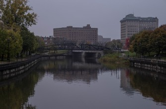 The Flint River flows past downtown Flint, Michigan October 22,2020. Flint, Michigan residents are still working through a water crisis and dealing with the Coronavirus (COVID-19) pandemic, Michigan reported a record 3,338 new Coronavirus cases in one day on Saturday October 24,2020. - Authorities say Flint's water meets federal safety guidelines, outperforming comparable cities. Residents remain unconvinced. On a Tuesday morning this month, blocks and blocks of cars waited near a church in the eastern part of the Midewestern city to receive value packs of bottled water. These giveaways still happen three days a week, some six years after residents began complaining that a decision to supply the city from the Flint River was making them sick. (Photo by SETH HERALD / AFP)