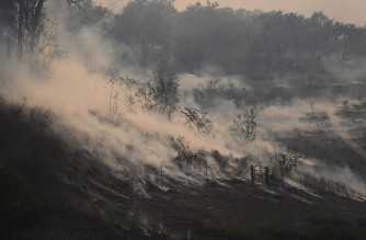 A hillside smolders in the Silverado Fire October 26, 2020 in Irvine, California. - The wind-driven fire broke out this morning and quickly scorched 2,000 acres in Orange County California. (Photo by Robyn Beck / AFP)