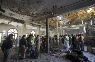 Security officials examine the site of a blast at a religious school in Peshawar on October 27, 2020. - At least four students were killed and dozens more wounded on October 27 when a bomb exploded during a class at their religious school in Pakistan, officials said. (Photo by Abdul MAJEED / AFP)