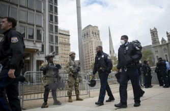 PHILADELPHIA, PA - OCTOBER 30: Police officers walk past as National Guard members monitor activity surrounding Philadelphia City Hall on October 30, 2020 in Philadelphia, Pennsylvania. In response to widespread unrest in the aftermath of Walter Wallace Jr.'s death, the National Guard arrived this afternoon to various locations throughout the city. The 27-year-old Walter Wallace Jr, a father of nine children, who Philadelphia police officers claimed was armed with a knife, was fatally shot by at least 14 total rounds.   Mark Makela/Getty Images/AFP
