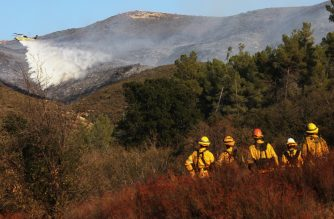 (File photo) SANTA CLARITA, CALIFORNIA - SEPTEMBER 28: Firefighters look on as a firefighting helicopter performs a water drop as the Martindale Fire burns in the Angeles National Forest on September 28, 2020 near Santa Clarita, California. Evacuations were ordered for residents near the area as wildfires have burned a record 3.75 million acres this year in California.   Mario Tama/Getty Images/AFP