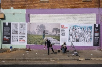 Red Cross setup crew members clear up their equipment  after sticking a poster on a wall at an initiative lead by the International Committee of the Red Cross (ICRC) to make regular South Africans relate to common struggles around the world caused by the COVID-19 coronavirus, by setting up interactive posters in Jeppestown, in Johannesburg on September 23, 2020. (Photo by Emmanuel Croset / AFP)