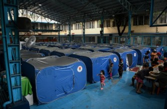 Children play next to tents at a temporary shelter during an evacuation of informal settlers living along coastal areas in Manila on November 1, 2020, as Super Typhoon Goni moved towards the Philippine capital. (Photo by Ted ALJIBE / AFP)