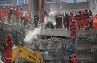 Search and rescue teams look for victims in the rubble of a collapsed building on November 01, 2020, in Izmir, after a powerful earthquake struck Turkey's western coast and parts of Greece. - Rescue workers were searching eight buildings in Izmir on November 1, despite dwindling hope for survivors, as the death toll of a powerful magnitude earthquake which hit western Turkey rose to 49. The 7.0-magnitude quake has also injured 896 in Turkey, the Turkish emergency authority AFAD said, after striking on Friday afternoon near the west coast town of Seferihisar in Izmir province. (Photo by OZAN KOSE / AFP)