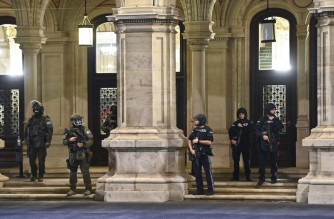 """Armed policemen stand guard in front of the main entrance of the State Opera in the center of Vienna on November 2, 2020, following a shooting. - Two people, including one attacker, have been killed in a shooting in central Vienna, police said late November 2, 2020. Vienna police said in a Twitter post there had been """"six different shooting locations"""" with """"one deceased person"""" and """"several injured"""", as well as """"one suspect shot and killed by police officers"""". (Photo by Joe Klamar / AFP)"""