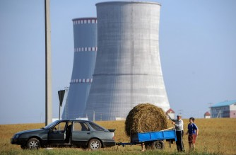 (FILES) In this file photo taken on August 19, 2017, people transport a bundle of straw close to the construction site of the first Belarus' nuclear power plant outside the town of Ostrovets, some 170 km northwest of Minsk. - Belarus on November 3, 2020 launched its controversial Russia-built nuclear power station despite safety concerns from neighbouring Baltic states three decades after the Chernobyl nuclear disaster. (Photo by Sergei GAPON / AFP)