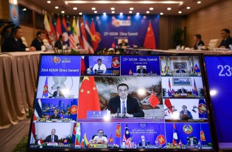 China's Premier Li Keqiang (C on screen) addresses counterparts during the ASEAN-China summit of the Association of Southeast Asian Nations (ASEAN), held online due to the COVID-19 coronavirus pandemic, in Hanoi on November 12, 2020. (Photo by Nhac NGUYEN / AFP)