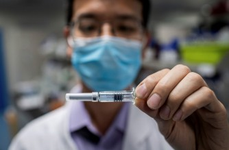 (FILES) This file photo taken on April 29, 2020 shows an engineer showing an experimental vaccine for the Covid-19 coronavirus that was tested at the Quality Control Laboratory at the Sinovac Biotech facilities in Beijing. (Photo by Nicolas ASFOURI / AFP) / TO GO WITH STORY virus-épidémie-santé-vaccins-Chine by Ludovic Ehret