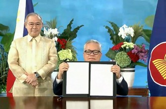 """A screen grab taken from Vietnam Host Broadcaster's November 15, 2020 live video shows Philippines Foreign Secretary Teodoro Locsin (L) standing next to the Philippines' Secretary of Trade and Industry Ramon Lopez as he holds up the agreement during the signing ceremony for the Regional Comprehensive Economic Partnership (RCEP) trade pact at the ASEAN summit that is being held online in Hanoi. (Photo by Handout / VIETNAM HOST BROADCASTER / AFP) / -----EDITORS NOTE --- RESTRICTED TO EDITORIAL USE - MANDATORY CREDIT """"AFP PHOTO / VIETNAM HOST BROADCASTER"""" - NO MARKETING - NO ADVERTISING CAMPAIGNS - DISTRIBUTED AS A SERVICE TO CLIENTS"""