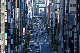 Traffic and business signage are seen along a street in Tokyo's Ginza district on November 16, 2020, as government data showed Japan's economy exited recession in the third quarter, growing a better-than-expected 5.0 percent following a record contraction. (Photo by Charly TRIBALLEAU / AFP)