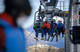 Skiers, some wearing protective face masks against the spread of the Covid-10 (novel coronavirus), ride a ski lift before hitting the slopes during the first snows of the season above the ski resort of Verbier in the Swiss Alps on November 15, 2020. - The coronavirus crisis shuttered Switzerland's ski resorts in the spring, but they are banking on tighter precautions and the Swiss love of the mountains to save them as the winter season begins. (Photo by Fabrice COFFRINI / AFP)