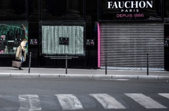 (FILES) In this file photo taken on September 08, 2020 a woman walks past a closed shop of French gourmet food company Fauchon in Paris. (Photo by STEPHANE DE SAKUTIN / AFP)