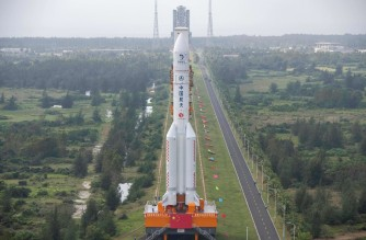 This photo taken on November 17, 2020 shows the Long March 5 rocket, which will launch China's Chang'e-5 lunar probe on November 24, being vertically transported to the launching area at the Wenchang Spacecraft Launch Site in southern China's Hainan province. (Photo by STR / AFP) / China OUT