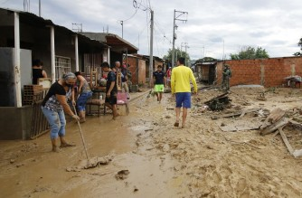 A woman tries to remove mud from the front of her house after heavy rains fell in Cucuta, Colombia, on November 18, 2020. - Heavy rains across the country have left at least 22 people dead and thousands homeless according to local authorities. (Photo by Schneyder MENDOZA / AFP)