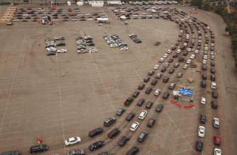 "This aerial view shows people waiting in line in their cars at a Covid-19 testing site at Dodger Stadium in Los Angeles, California, November 18, 2020. - As case numbers spike health officials are warning that Los Angeles county is facing ""one of the most dangerous moments in this pandemic,"" and are defending new, stricter business and social gathering restriction, including a curfew which will require restaurants, breweries, bars and non-essential retail businesses to be closed from 10pm to 6am. (Photo by Robyn Beck / AFP)"