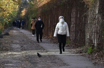 People wearing face masks walk along the Cheonggye stream in downtown Seoul on November 23, 2020. (Photo by Jung Yeon-je / AFP)