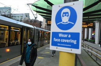 A person wearing a face covering due to the COVID-19 pandemic, waits to board a tram in Manchester, northwest England, on November 26, 2020. - London will escape the tightest restrictions once England's national coronavirus lockdown ends next week, the government said Thursday, but major cities including Manchester and Birmingham face at least two more weeks of tough rules. England will return to a regional tiered system when the national regulations end on December 2, with those areas suffering the worst case rates entering the highest Tier 3. (Photo by Oli SCARFF / AFP)
