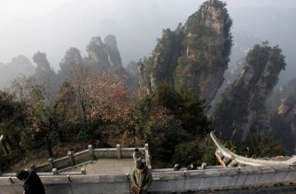 "(FILES) In a file picture taken on December 13, 2005 a tourists admire various peaks at the Zhangjiajie National Forest Park, China's first national forest reserve in Zhangjiajie, central China's Hunan province.  A city in central China has renamed a mountain after the US blockbuster movie ""Avatar,"" which set a Chinese box office record until its run in the country was cut short. The majestic peak in Hunan province previously known as ""Heaven and Earth Pillar"" or ""South Sky Pillar"" has been officially renamed ""Avatar Hallelujah Mountain,"" the Zhangjiajie city government said in a statement on January 26, 2010.  AFP PHOTO/FILES/GOH CHAI HIN (Photo by AFP FILES / AFP)"