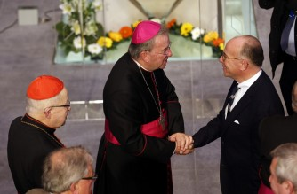 Apostolic Nuncio Luigi Ventura (L) shakes hands with French Interior Minister Bernard Cazeneuve during the inauguration of Notre-Dame of Creteil Cathedral in Creteil on September 20, 2015.  AFP PHOTO / FRANCOIS GUILLOT (Photo by FRANCOIS GUILLOT / AFP)