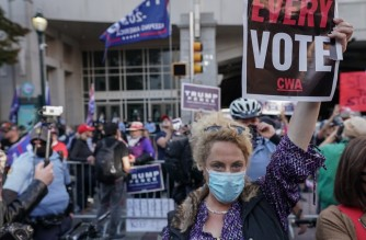 PHILADELPHIA, PENNSYLVANIA - NOVEMBER 06: A demonstrator holds up a sign during a Voting and Democracy celebration at the Philadelphia Convention Center on November 06, 2020 in Philadelphia, Pennsylvania.   Jemal Countess/Getty Images for MoveOn/AFP
