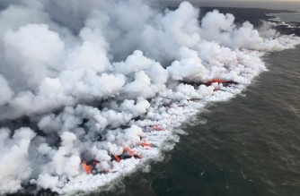 """This image obtained June 26, 2018 from the US Geological Survey shows the lava entering the sea and releasing multiple laze plumes at Kilauea Volcano, Hawaii. (Photo by HO / US Geological Survey / AFP) / RESTRICTED TO EDITORIAL USE - MANDATORY CREDIT """"AFP PHOTO / US Geological Survey/HO"""" - NO MARKETING NO ADVERTISING CAMPAIGNS - DISTRIBUTED AS A SERVICE TO CLIENTS"""