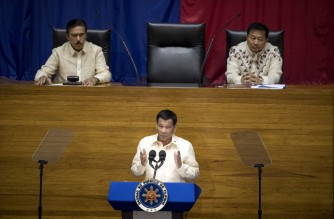 Philippine President Rodrigo Duterte (C) gestures as he delivers his state of the nation address, while Senate President Vicente Sotto III (L) and House Speaker Pantaleon Alvarez (R) listen, at Congress in Manila on July 23, 2018. (Photo by NOEL CELIS / AFP)